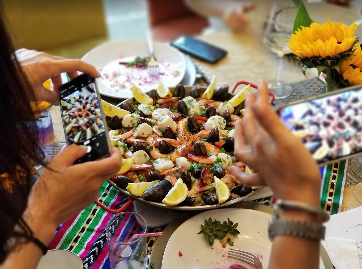 people taking pictures of paella on table