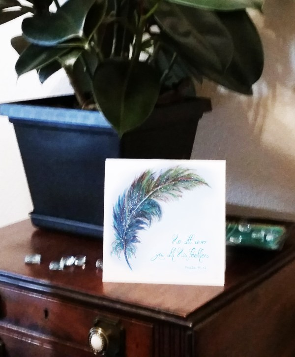 Watercolor Feather Card Image on brown table with plant