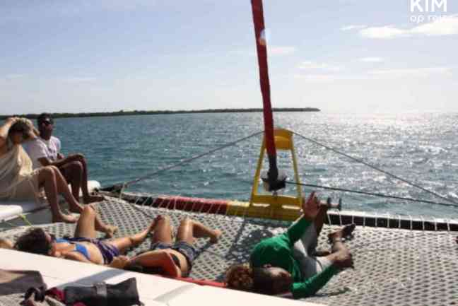 Mensen zonnen op het dek van de Raggamuffin catamaran tijdens het varen