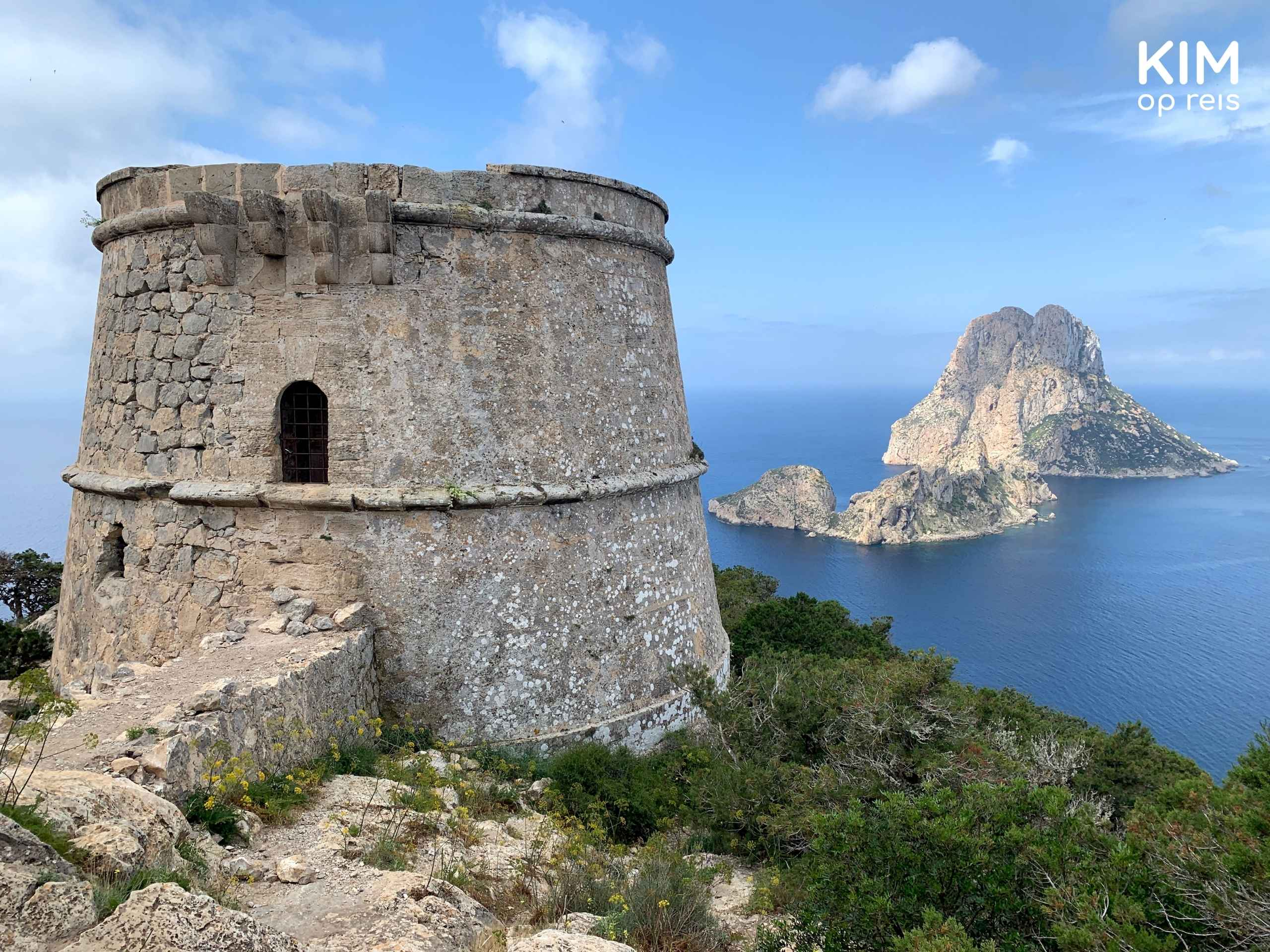 Torre de Pirata Ibiza: a round, low tower with the rock formation Es Vedra . in the background