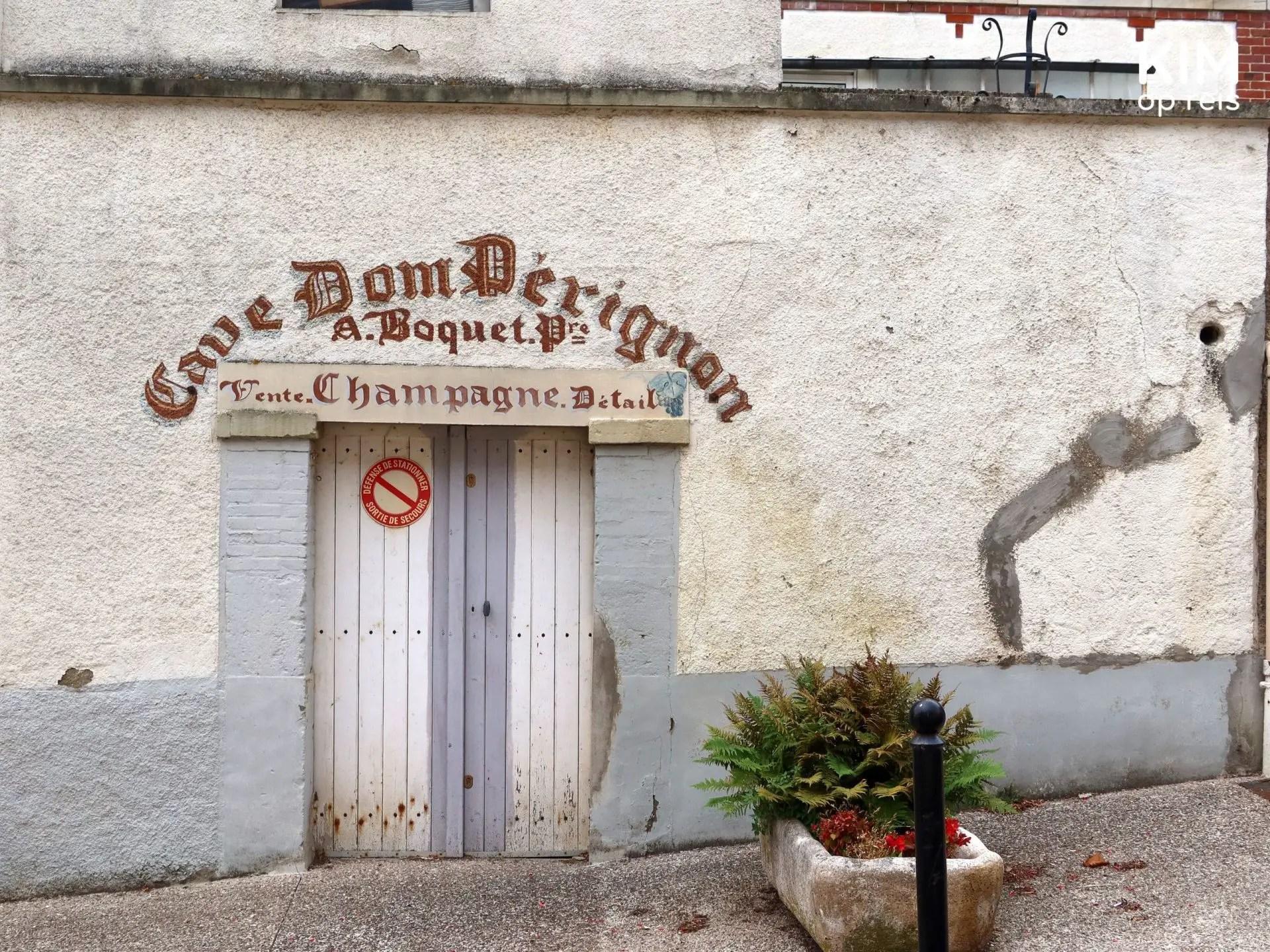 Dom Pérignon Hautvillers: oud, verkleurd wit huis met daarop Cave Dom Perignon