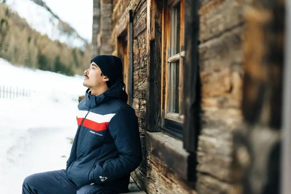 Duurzame winterjas: jongen zit voor een houten blokhut voor zich uit te staren