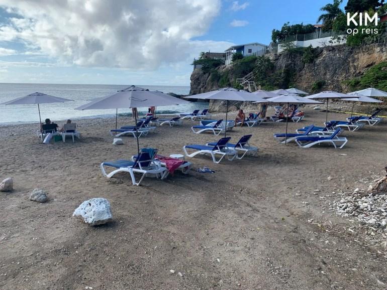 playa Grandi Curaçao: strand met enkele strandbedjes, op de achtergrond rotsen met daarom huizen