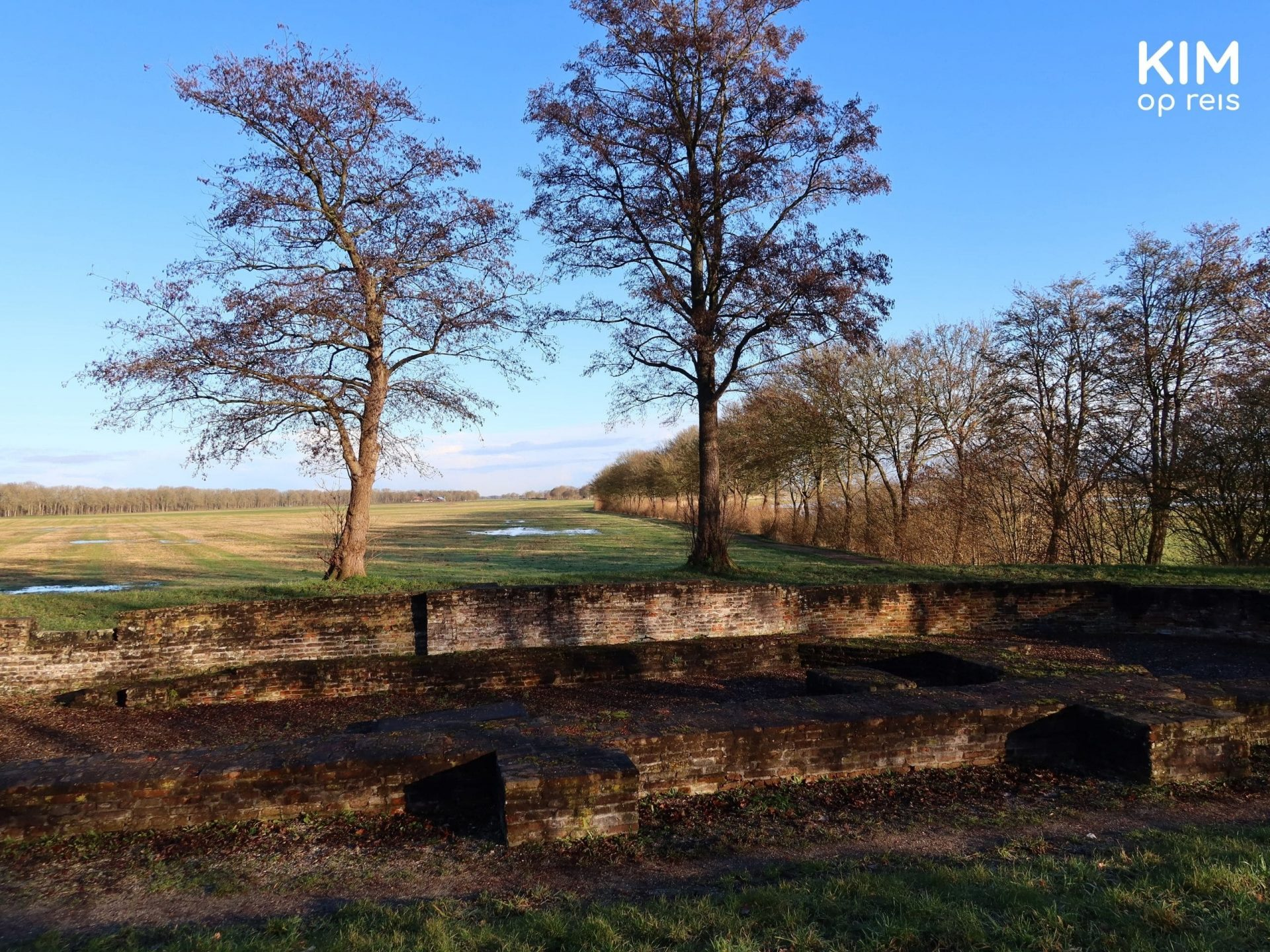 Schokland church ruin: extensive landscape with the foundations of the church walls in the foreground