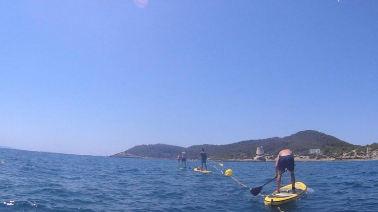 Balanceren SUPboard Ibiza - drietal mensen met een SUPboard waarbij het duidelijk niet zo goed gaat