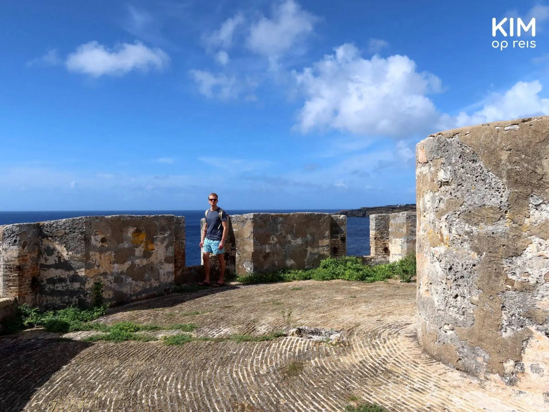 Bezienswaardigheid Curaçao Fort Beekenburg: jongen staat op het bovenste gedeelte van het fort