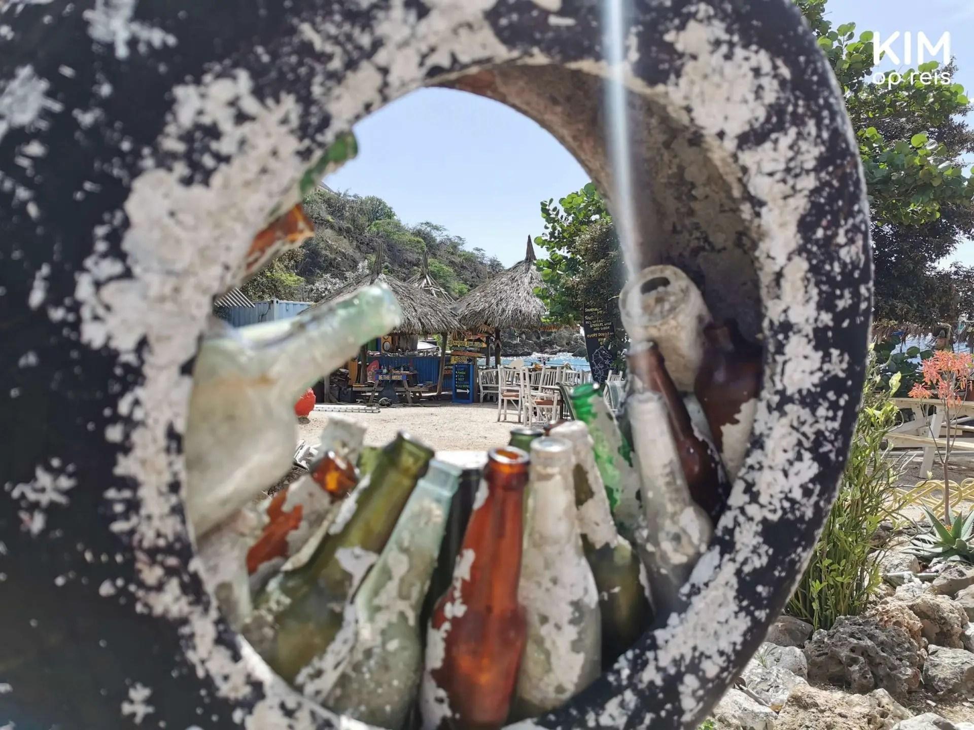 Bezoek Tugboat Beach Bar: oude autoband met verweerde flesjes geven een doorkijkje de beach bar in