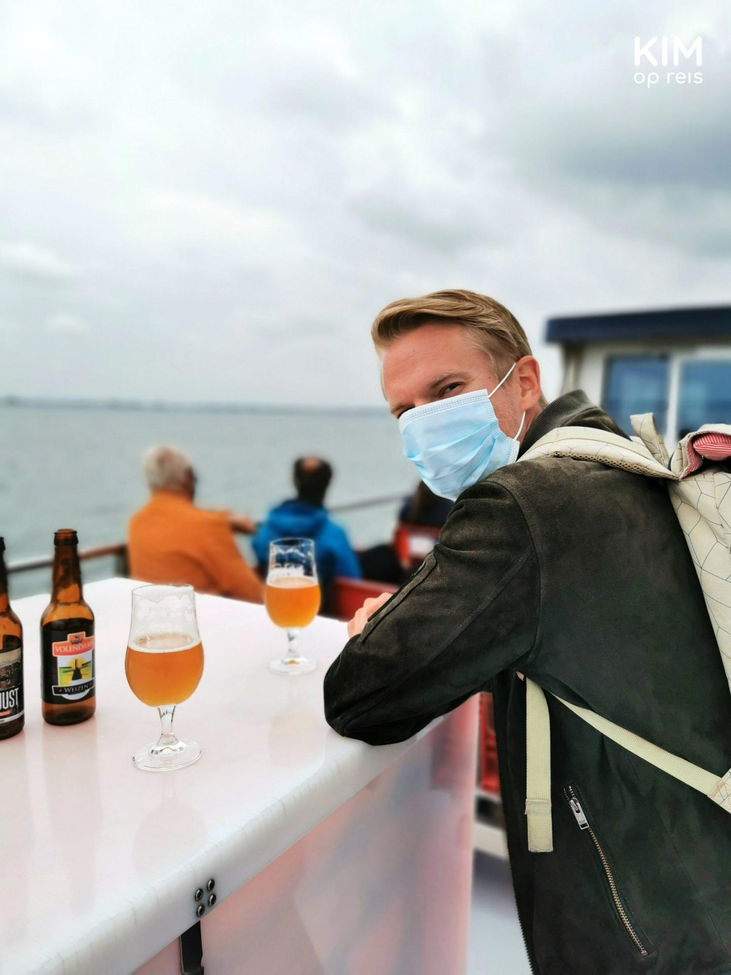 Drinking beer on the Marken Express - Patrick leans on the boat with a mouth mask on; there are two beers in front of him