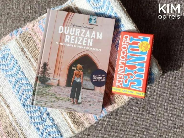 Duurzaam Reizen boek cadeautip: boek ligt op de bank, op een kleedje met een reep Tony's Chocolonely ernaast