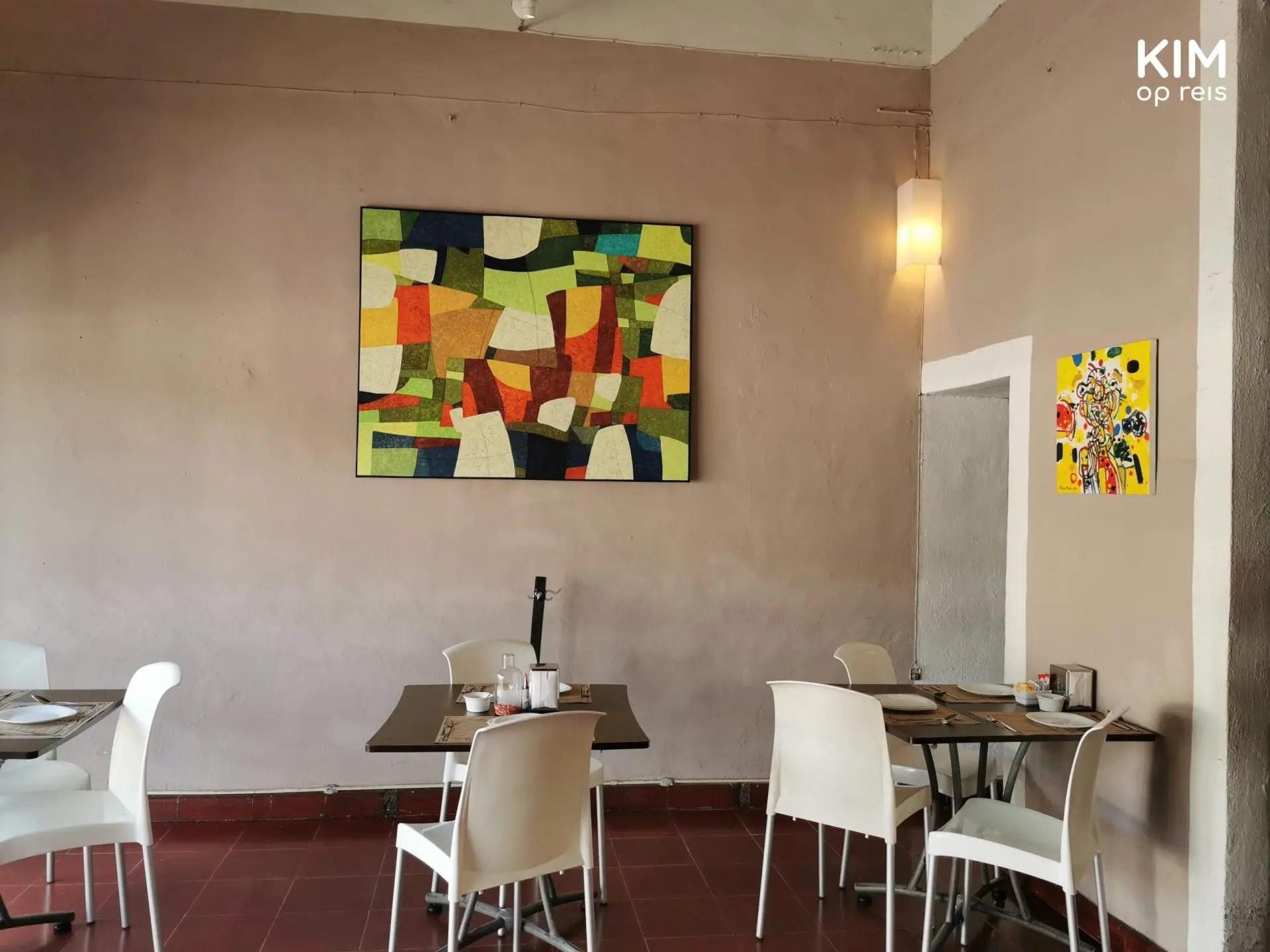El Manjar Blanco: sober interieur met plastic stoelen, een tweetal fleurige schilderijen haalt het geheel op