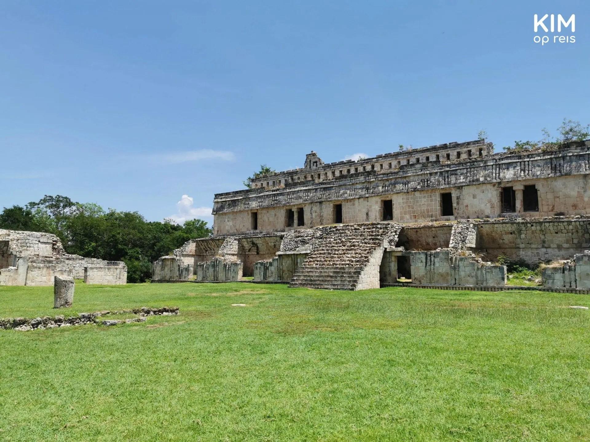 Kabah Ruta Puuc: groot overblijfsel van een gebouw op een groen grasveld