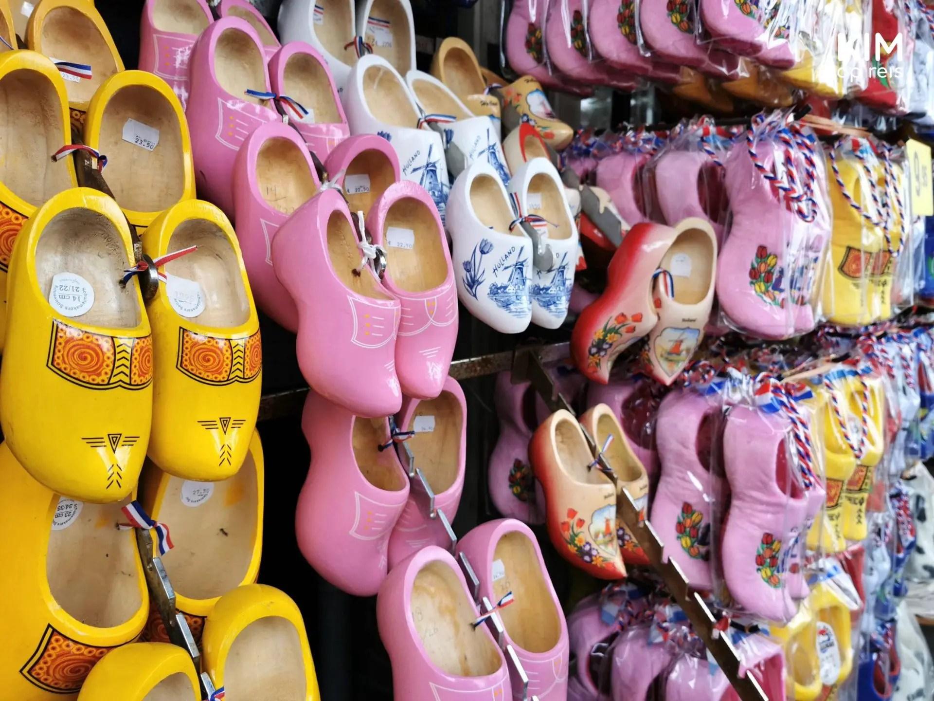 Klompen als souvenir Volendam - gele, roze en delfts blauw gekleurde klompen uitgestald aan de muur
