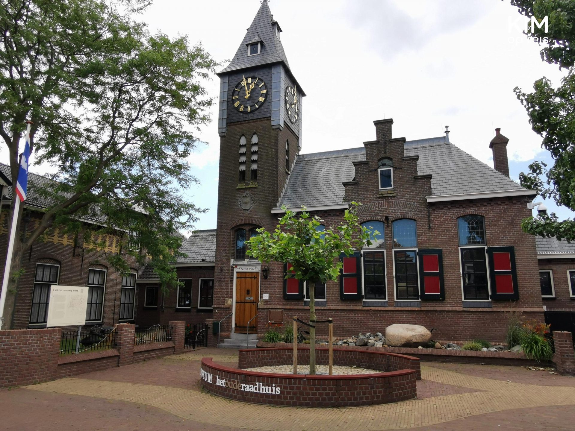 Museum het Oude Raadhuis - the exterior of the museum with a small flowerbed and a stately clock on the tower