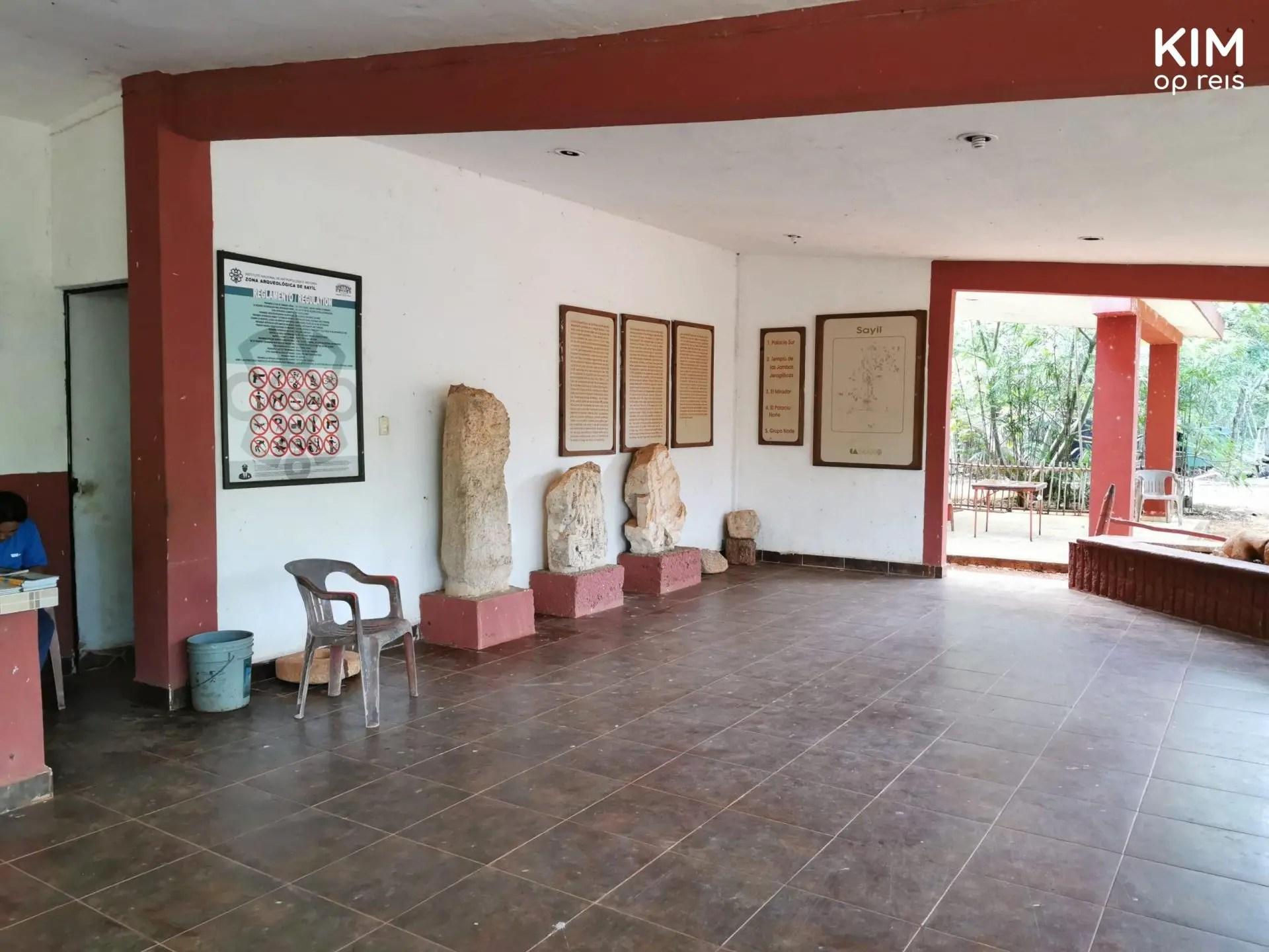 Museumruimte Sayil: vrij lege ruimte met tegen de muur enkele stukken steen en wat posters