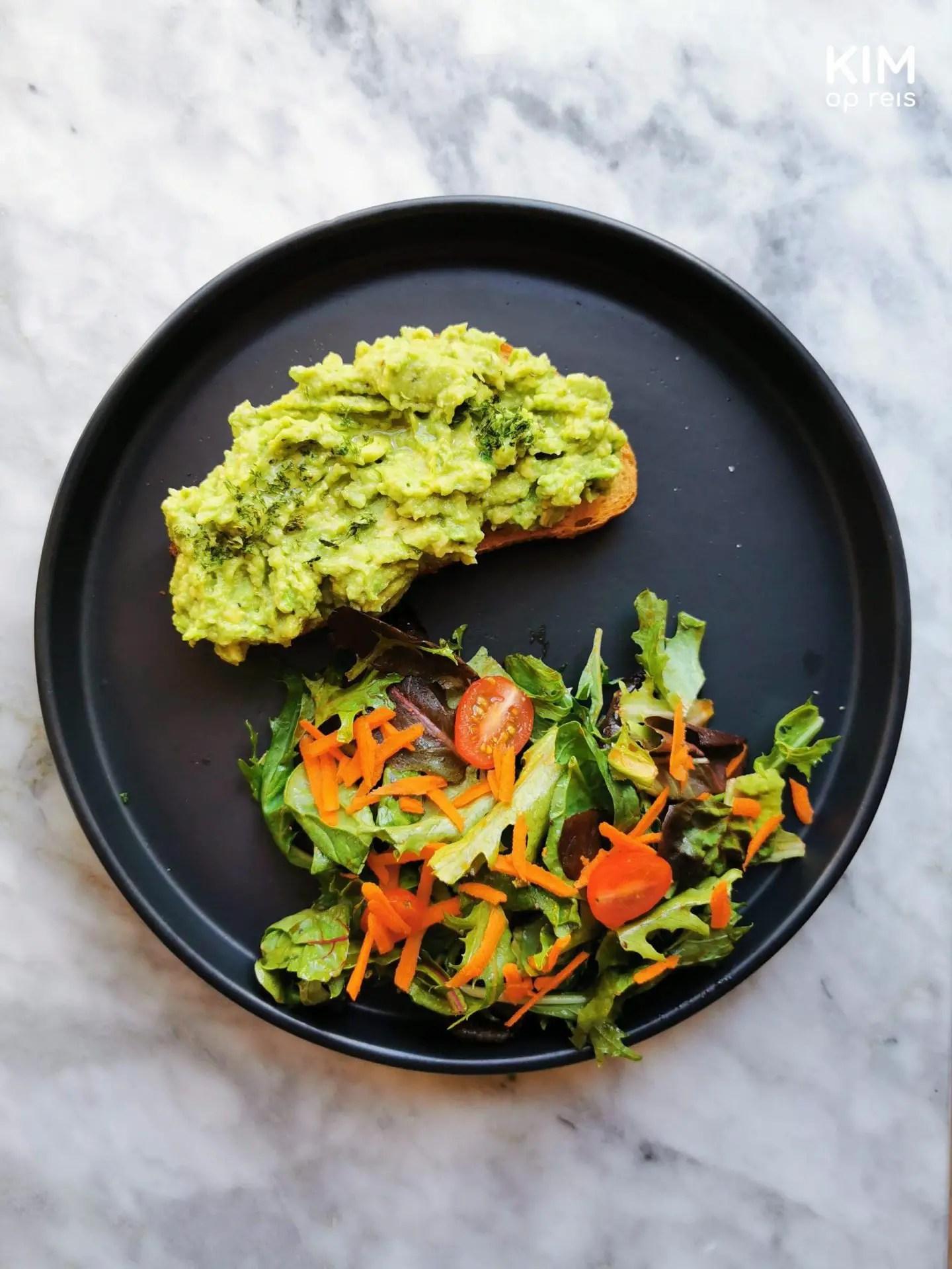 Ontbijt Mérida Marmalade: donker bord op een marmer tafel met een toast met avocado en ernaast een salade