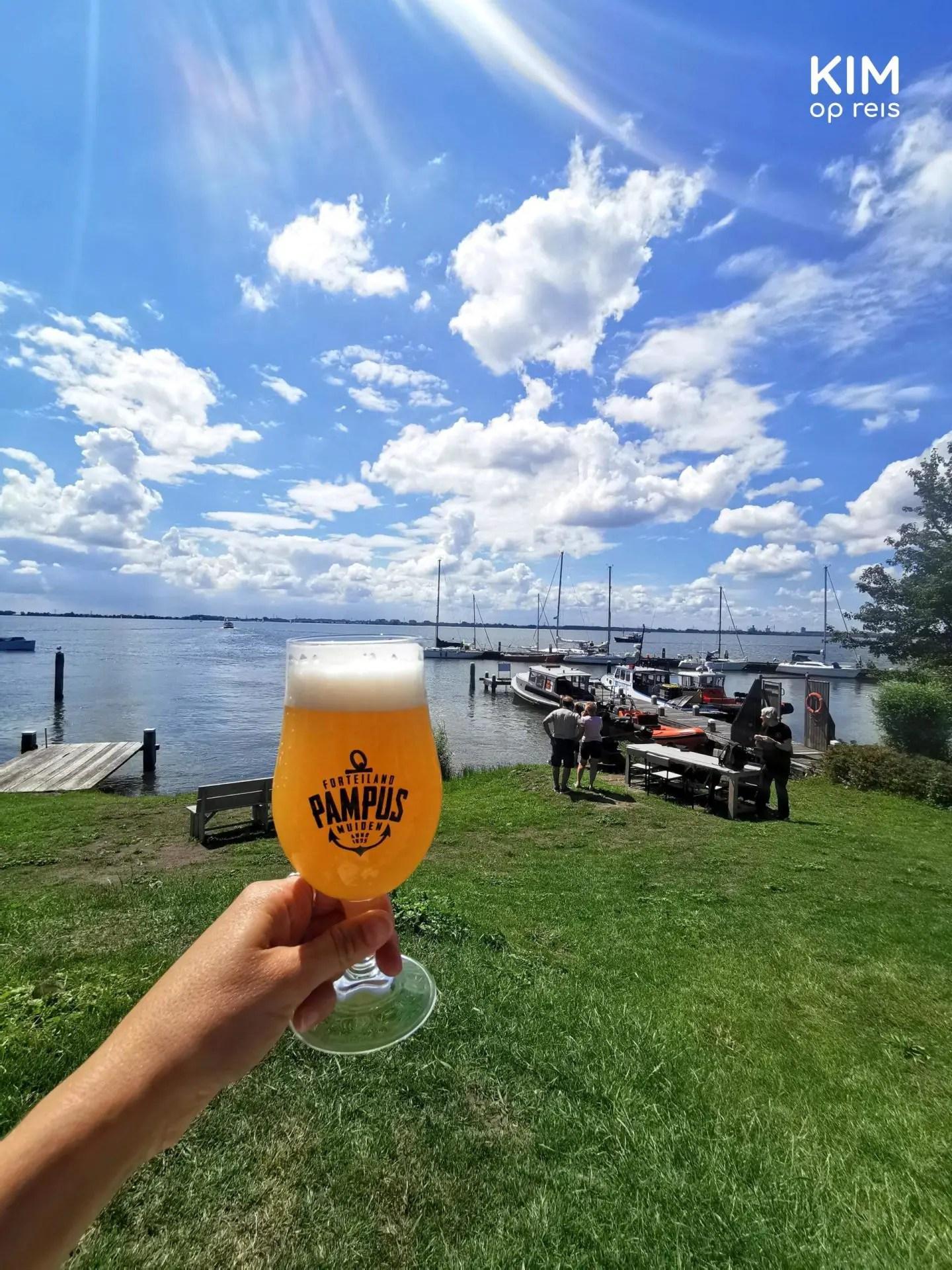 Pampus bier: hand houdt een glas bier met het logo van Pampus op tegen een achtergrond van de steiger en water