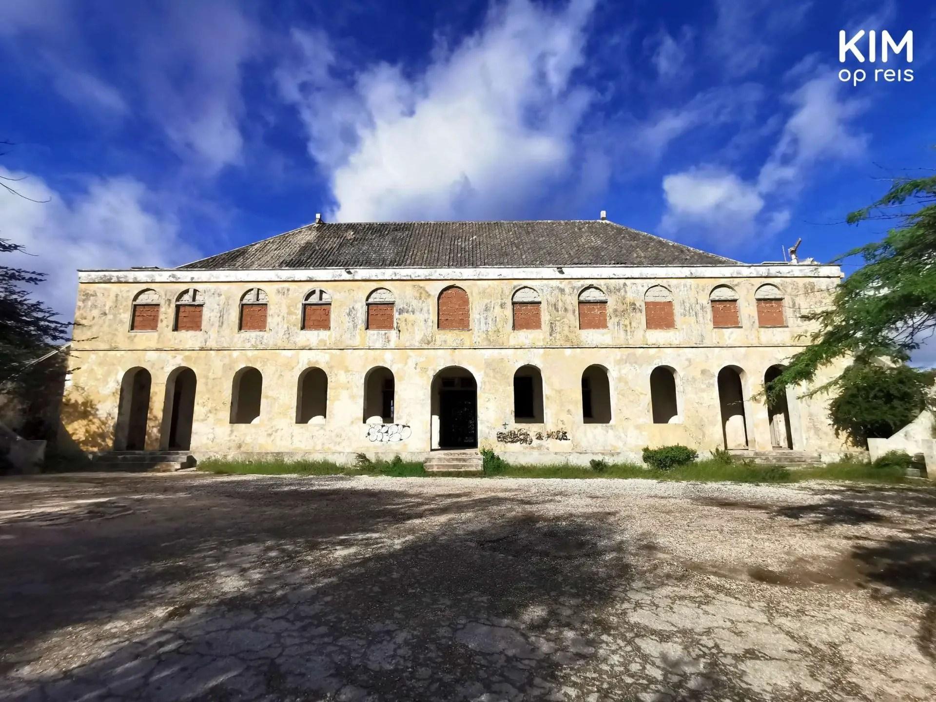 Quarantainegebouw Curaçao verlaten: breed gebouw met grote poorten en boven afgesloten ramen, afgebladderde gele verf