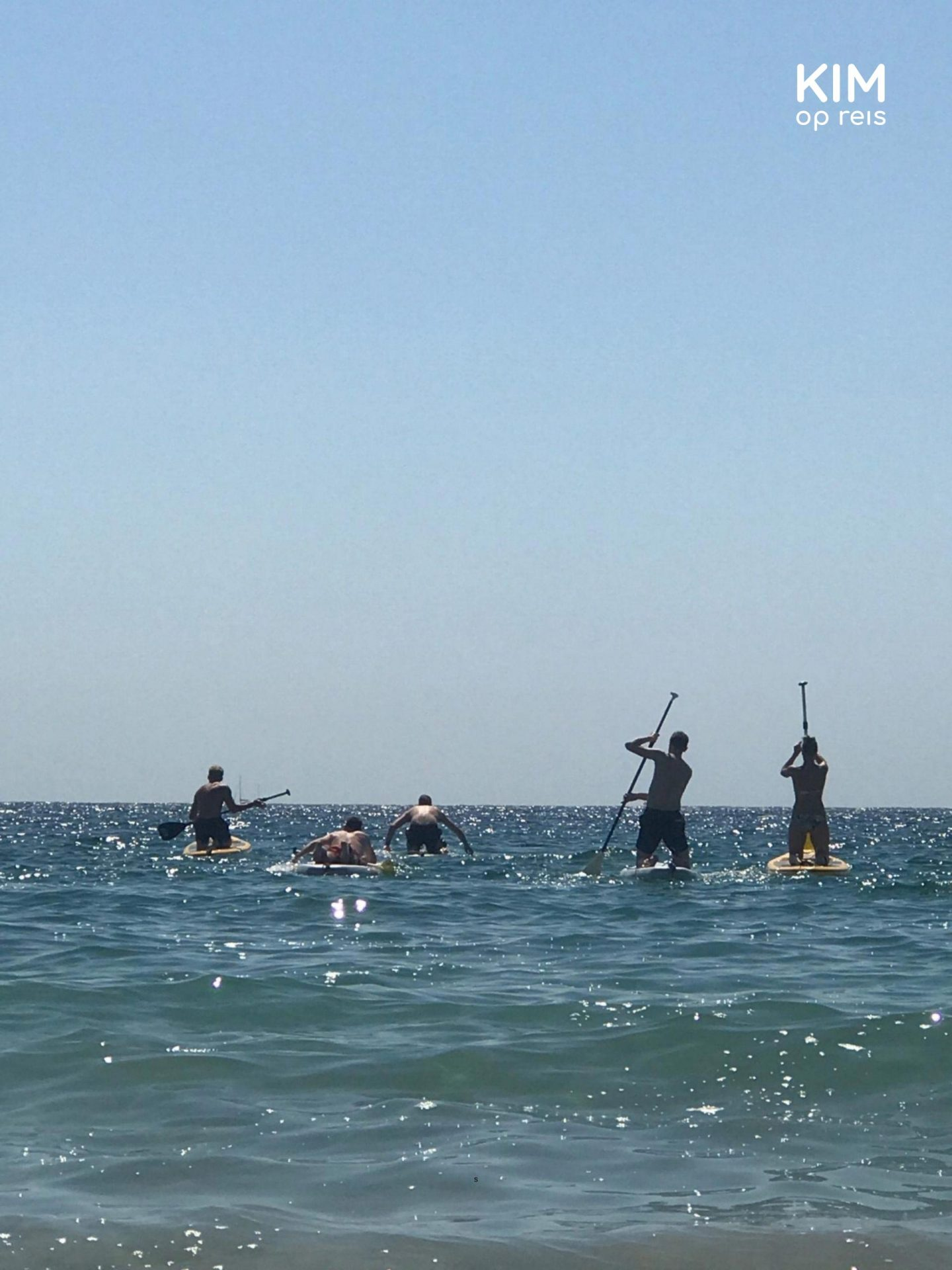 SUP Ibiza: A group of people goes out to sea, still sitting on the knees on the sup board