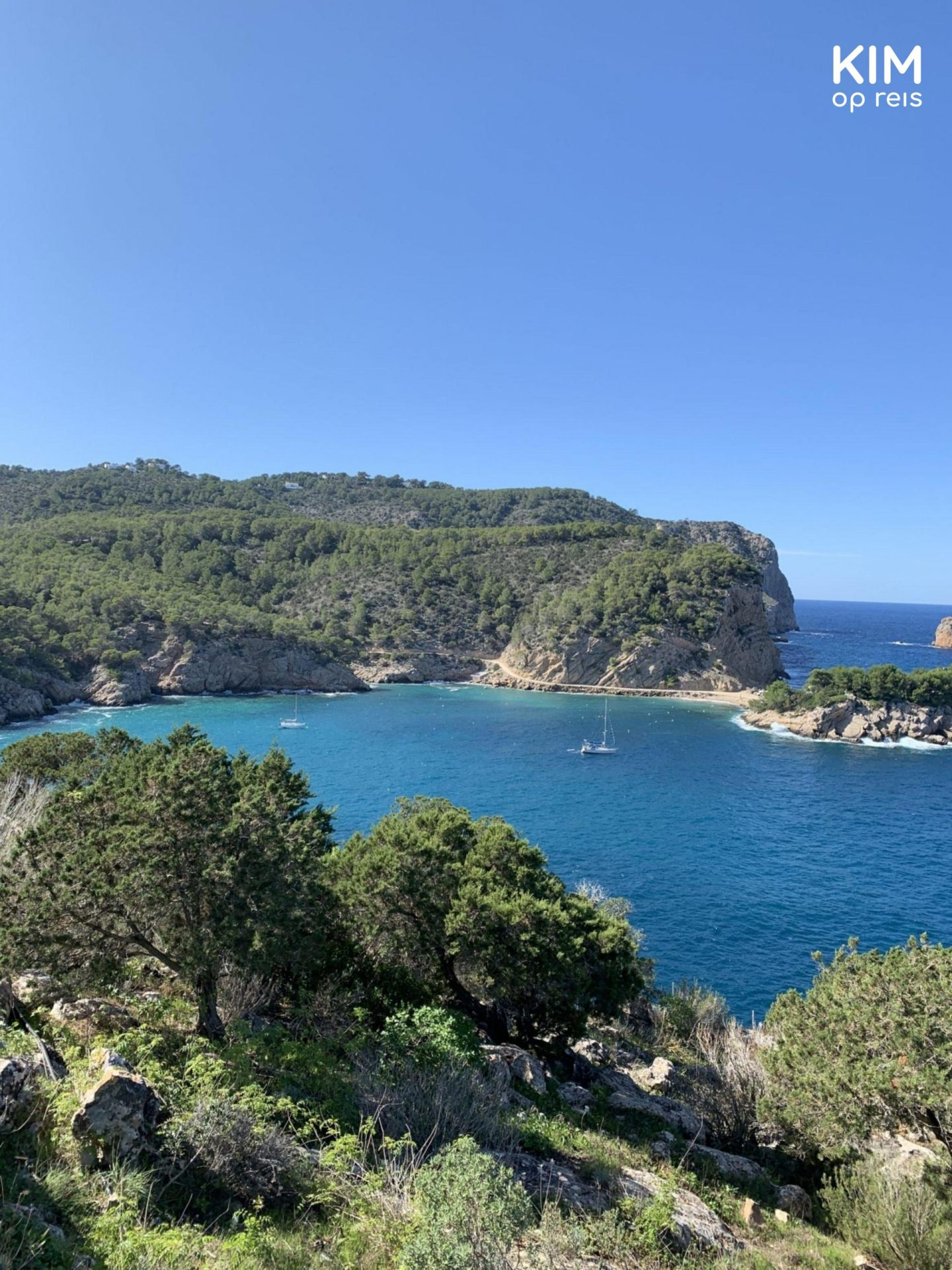 View Cova de Can Marca - bay with dense rocks and a sailboat in the water