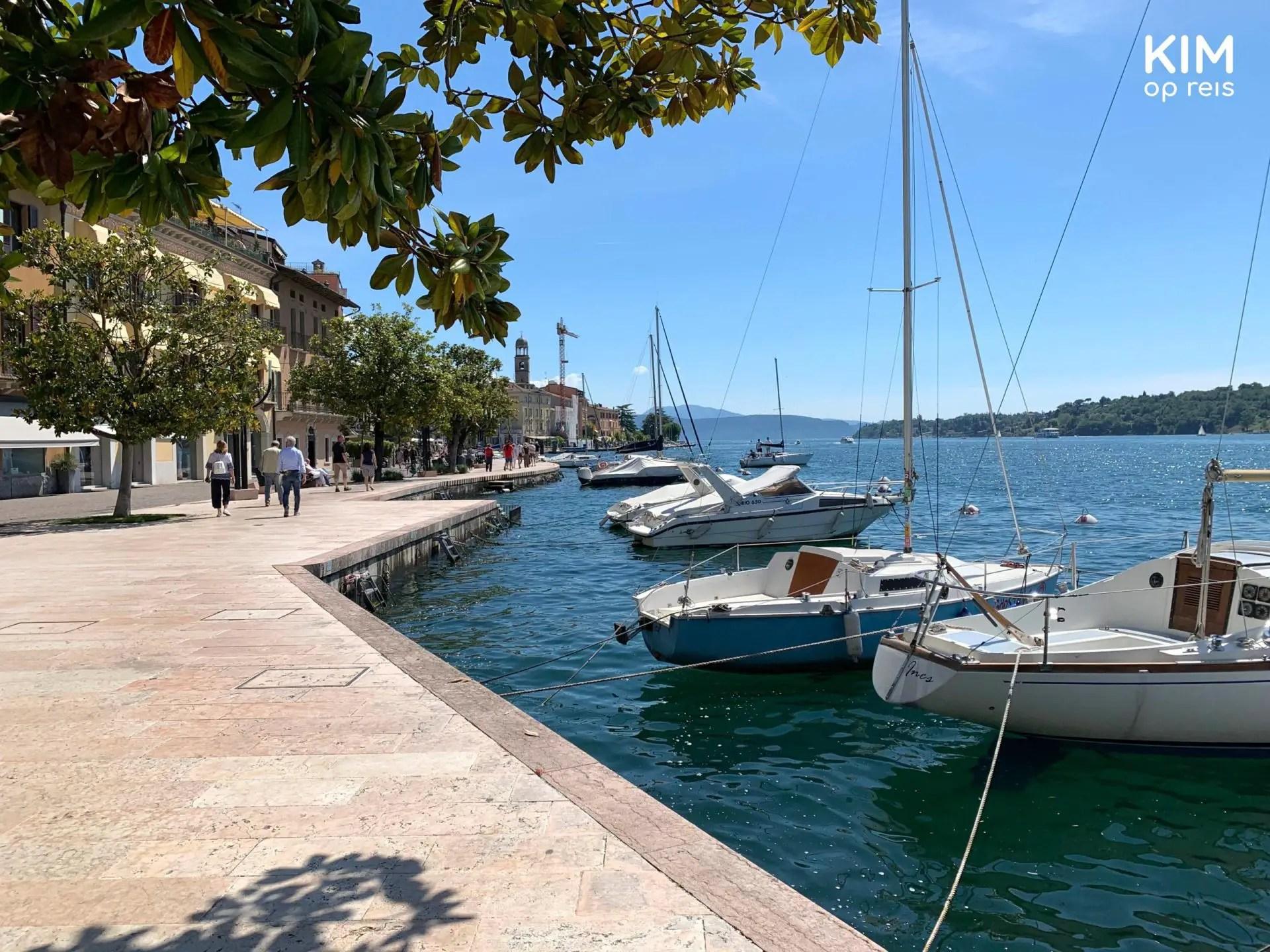 Wandelboulevard Salò - door een boom overdekt stukje van de wandelboulevard met daarvoor enkele bootjes