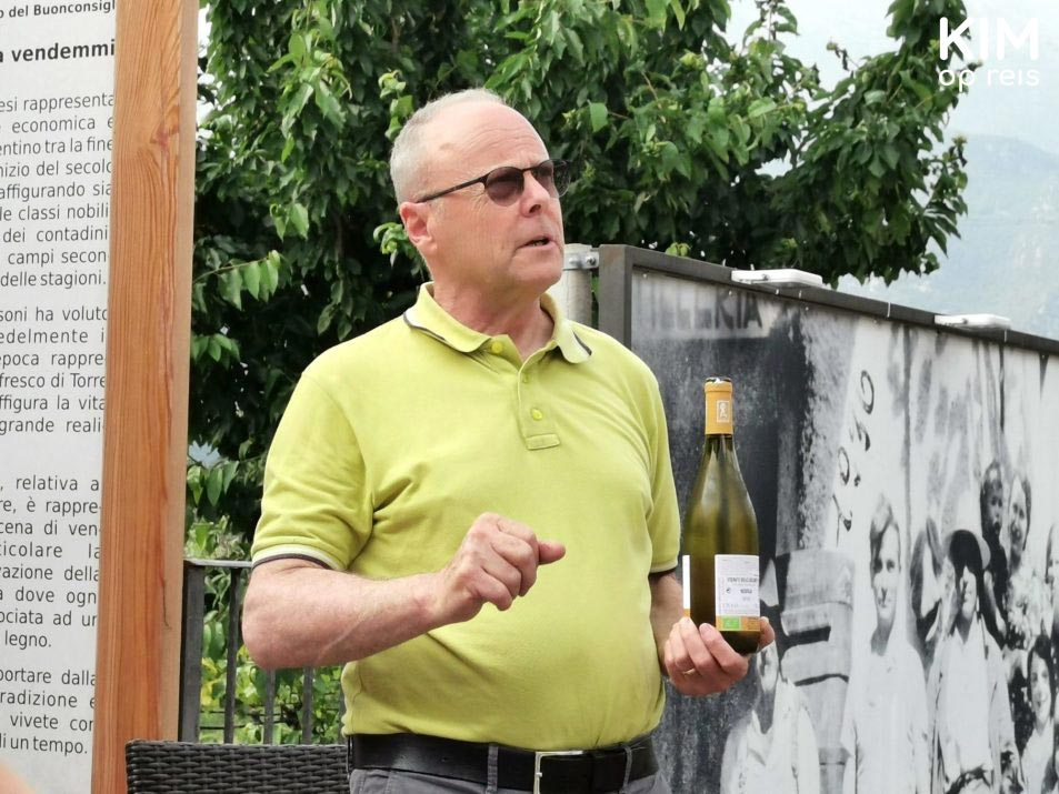 Wine tasting Cantina Pisoni - owner explains with a bottle of wine in his hand