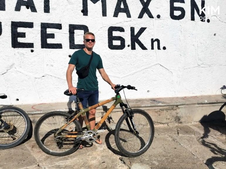 activiteiten excursies tours ibiza - jongen staat met een bamboe fiets voor een witte muur met letters