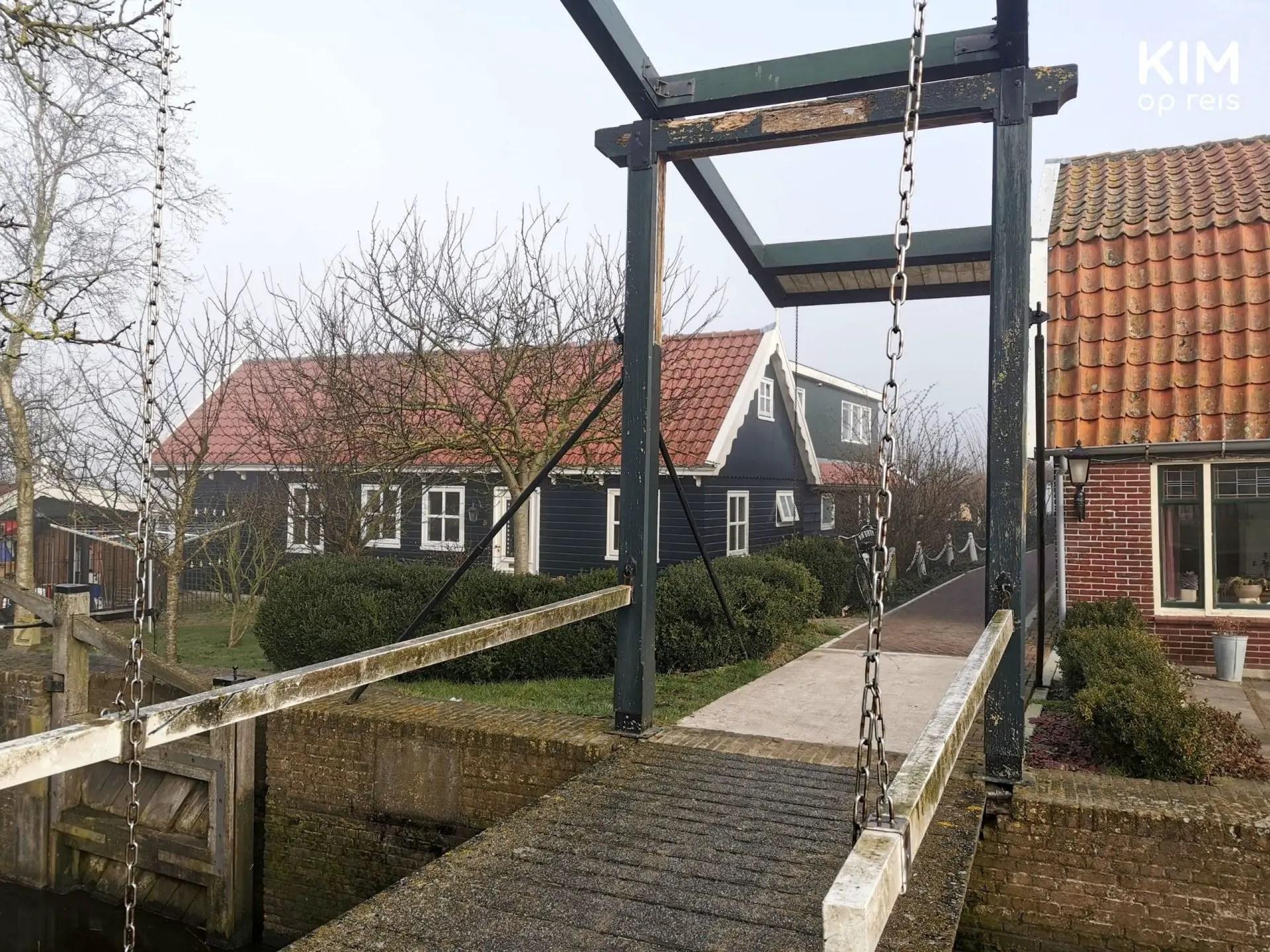 dorp en eiland de Woude: kleine houten ophaalbrug met daarachter enkele huizen.