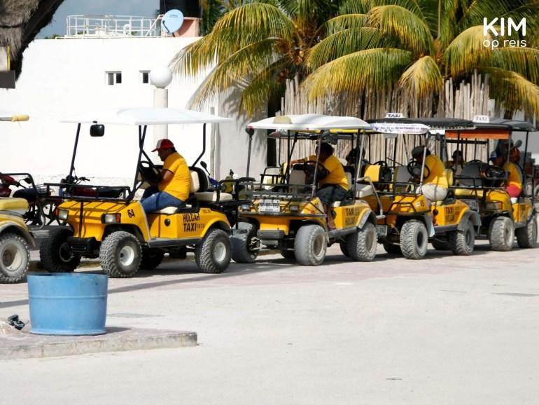 Isla Holbox golfkarretjes: achter elkaar geparkeerde golfkarretjes met daarin chauffeurs die wachten op klanten