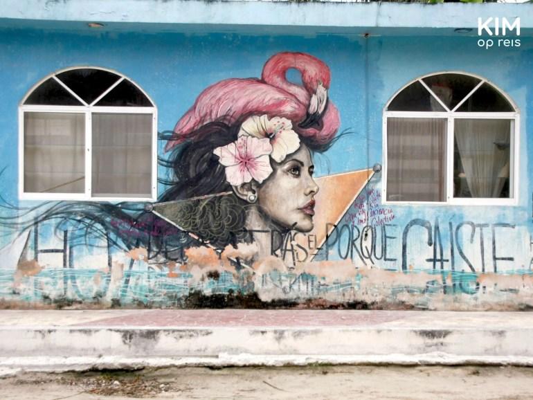 Isla Holbox street art meisje flamingo: muurschildering van vrouw met een bloem in d'r haar en een flamingo op haar hoofd