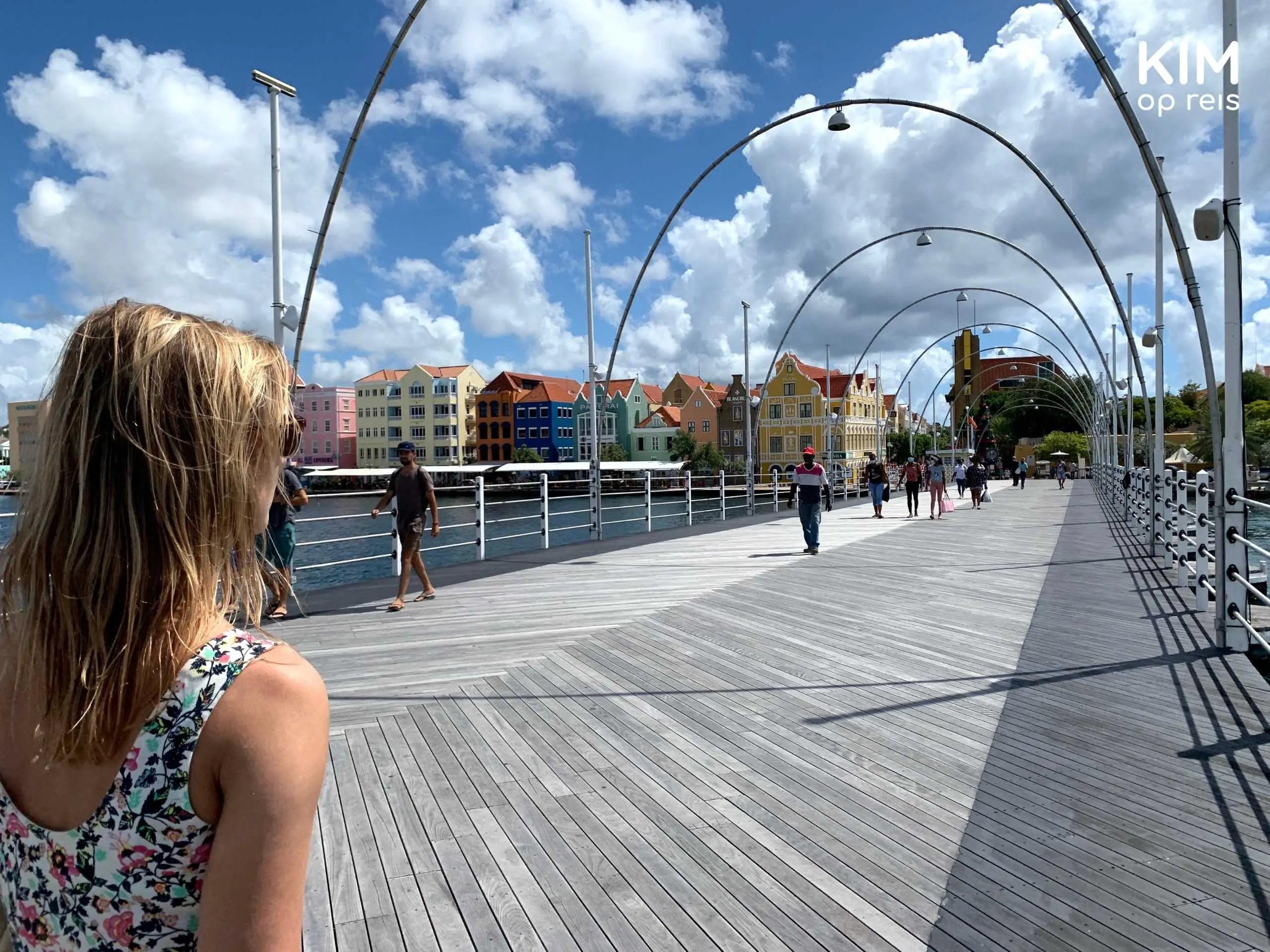 Willemstad Pontjesbrug Curaçao: in de linkerhoek wandelt een vrouw de brug op, voor haar ligt de brug waarop enkele mensen haar tegemoet komen