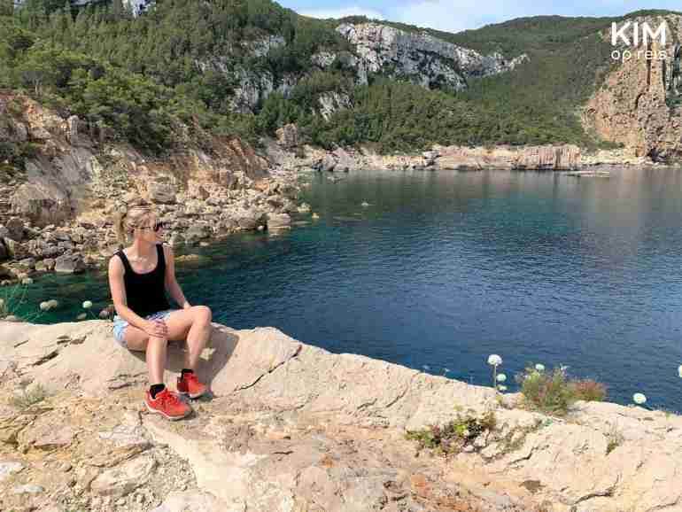 Rest walking Cala d'Albarca: Kim sits on the edge of a cliff, overlooking the bay