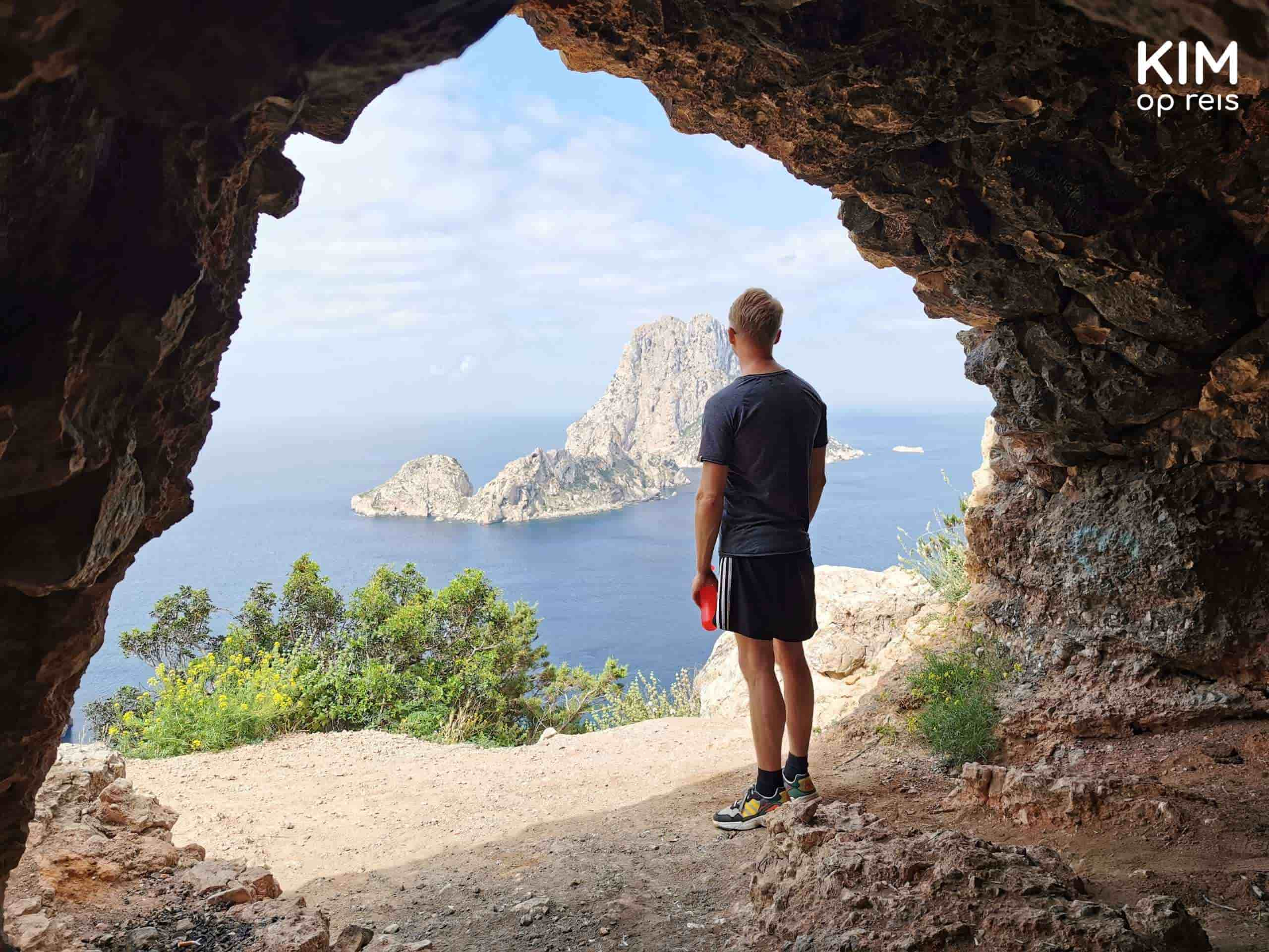 hippie cave Es Vedra: a man stands in the opening of the cave looking at Es Vedra