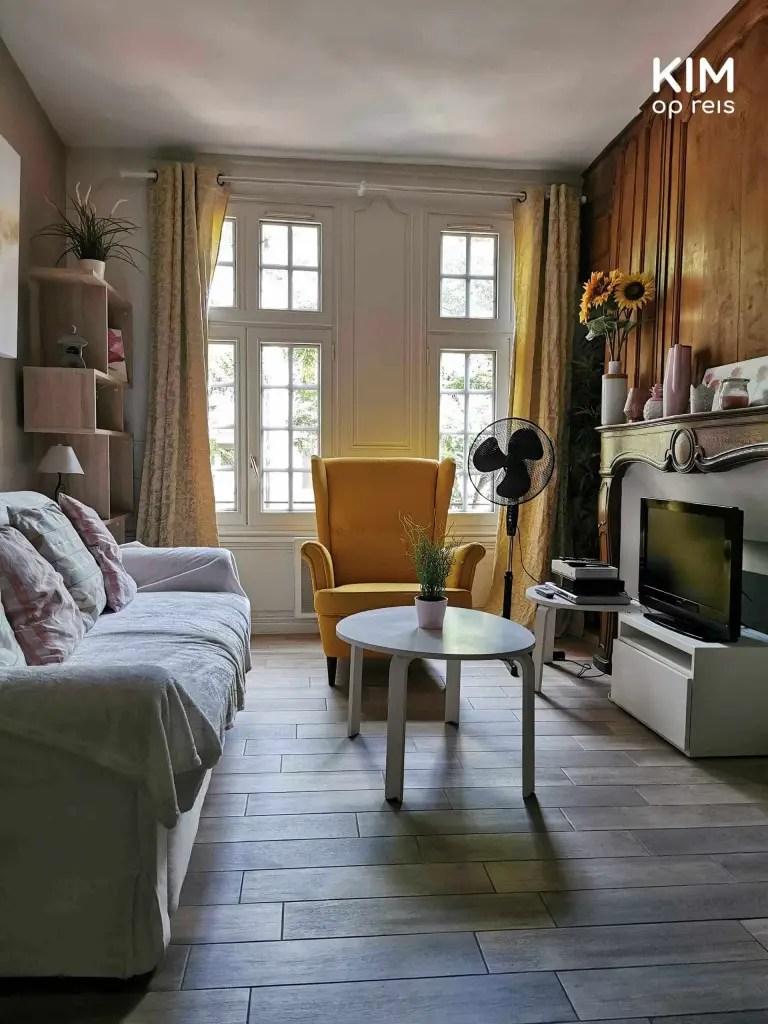 Airbnb Troyes: woonkamer met bankje, tafeltje en gele stoel voor het raam