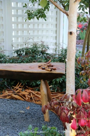 Almost hidden in a side garden, hand-furled timber cones reinforce the bespoke nature of the stool on which they're placed.