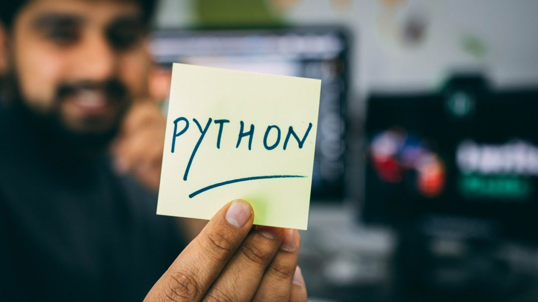 Man holding a piece of paper with the word python written on it and underlined