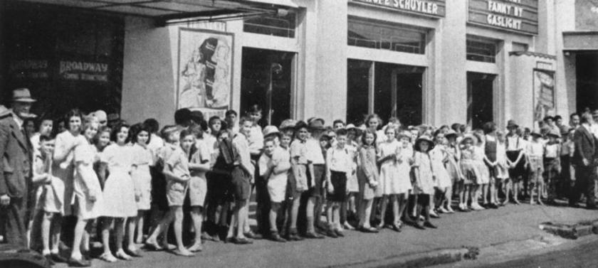 School children lined up on the footpath outside a cinema in Brisbane, 1945