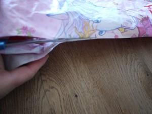 Drachen basteln mit Kindern ist Schneidearbeit: Nun schnippeln wir eine Seite der Plastiktüte in der Mitte durch. Foto (c) kinderoutdoor.de