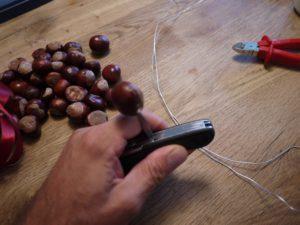 Kinder werken mit dem Taschenmesser und durchbohren die erste Kastanie vier Mal. foto (c) kinderoutdoor.de