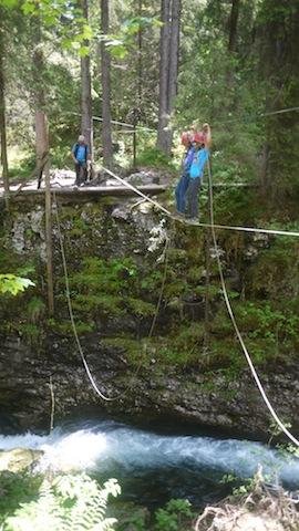 Gemeinsam macht es doppelt so viel Spaß: Gut gesichert arbeiten sich die Kinder vorsichtig über die Seilbrücke. Unten rauscht der Wildbach. foto (c) kinderoutdoor.de