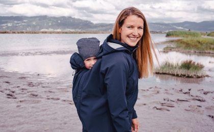Frau mit Baby am Strand - Babytragejacken