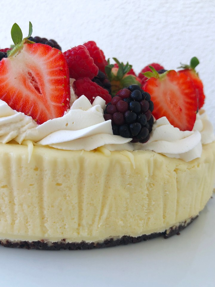 A keto friendly white chocolate cheesecake with a chocolate crust, topped with whipped cream and fresh berries.
