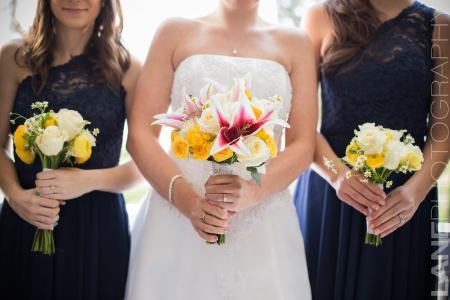 Bride with Bridesmaids in dark navy dresses holding bouquets of white and yellow flowers