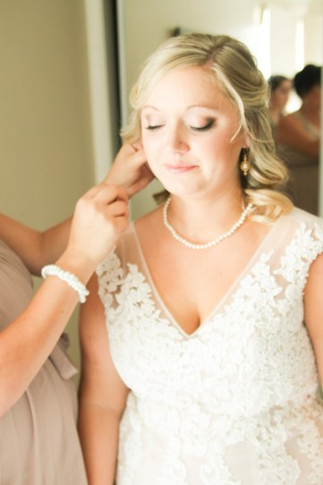 Bride in beautiful pearl necklace borrowed from her grandmother, gets help with her earrings