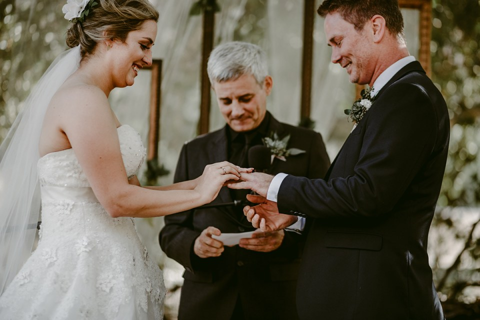 Bride and Groom gleefully exchange rings during wedding ceremony