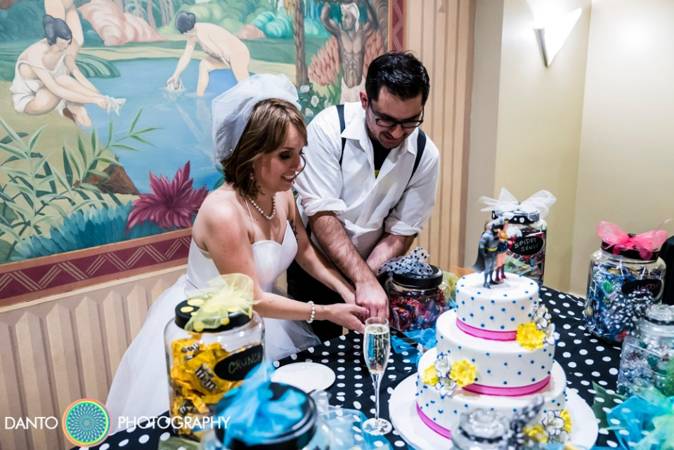 Bride and Groom cut wedding cake with Batman and Wonder Woman cake toppers