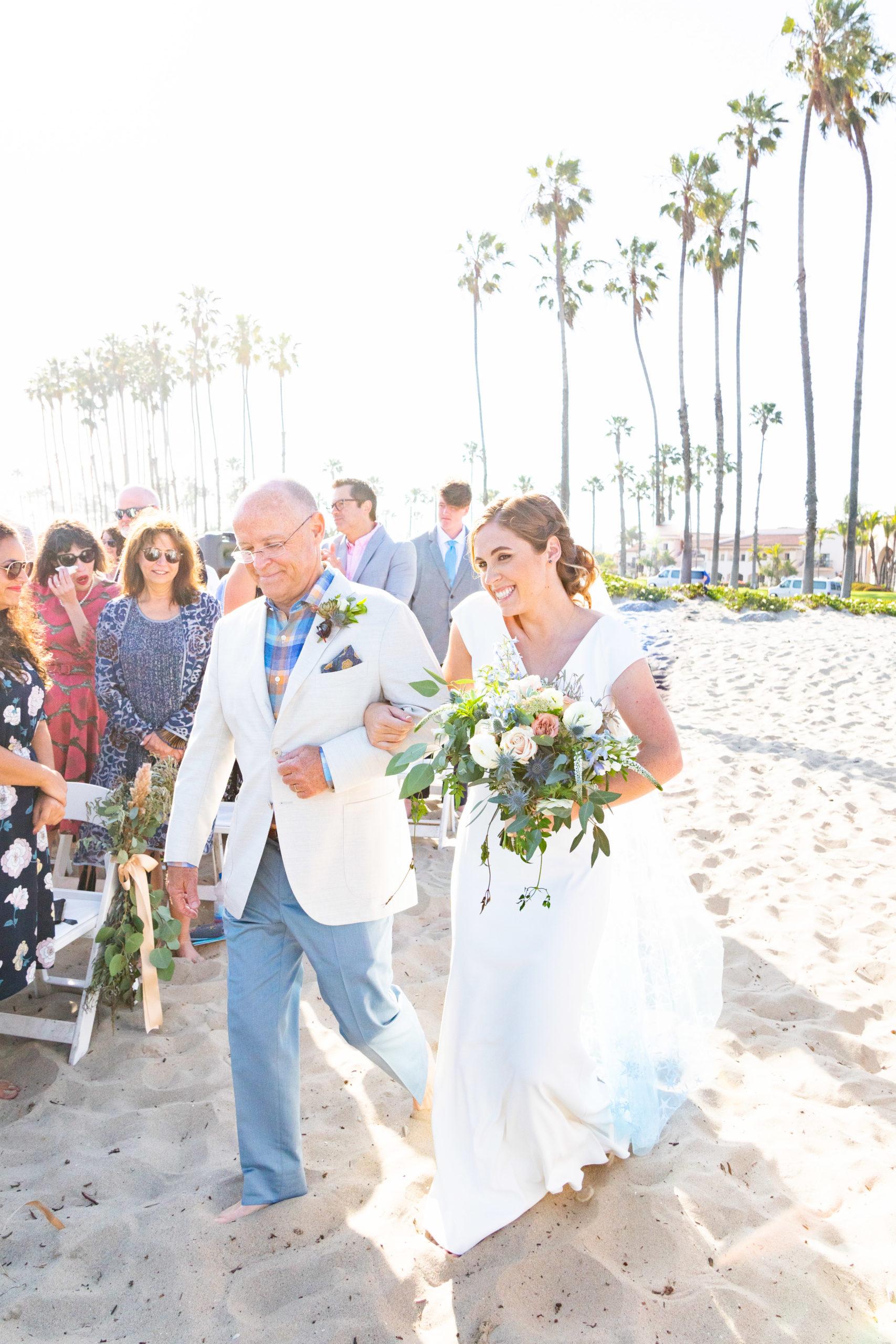 Dad walking bride down beach aisle