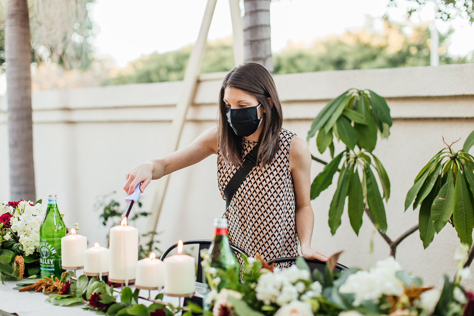 Wedding planner lights candles wearing a mask
