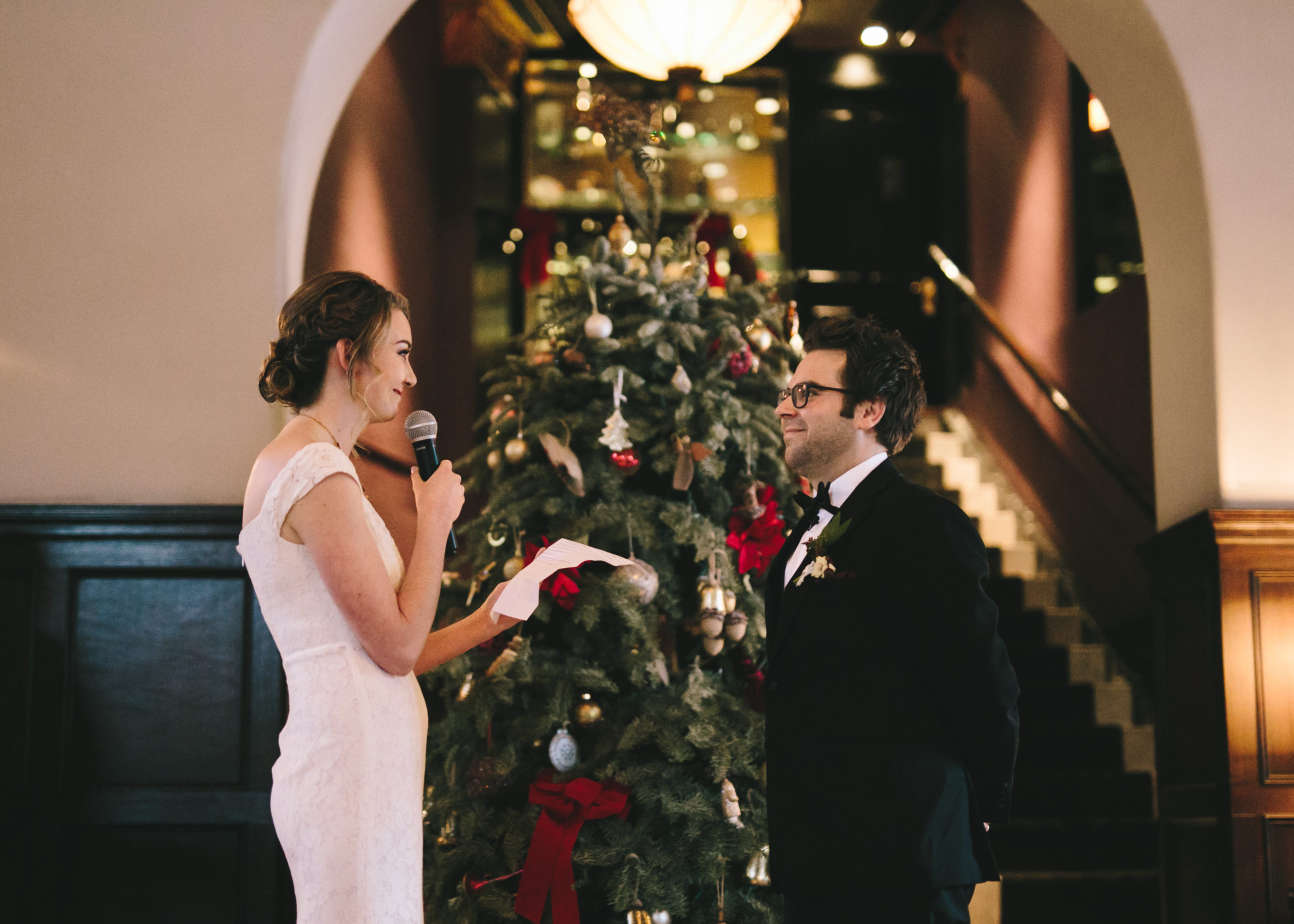 Bride reads vows to groom with Christmas tree in background
