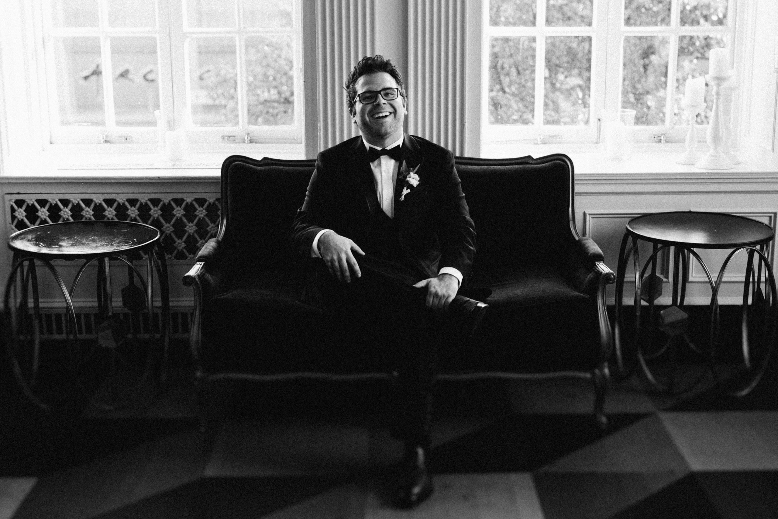 Groom smiling sitting on couch in black and white