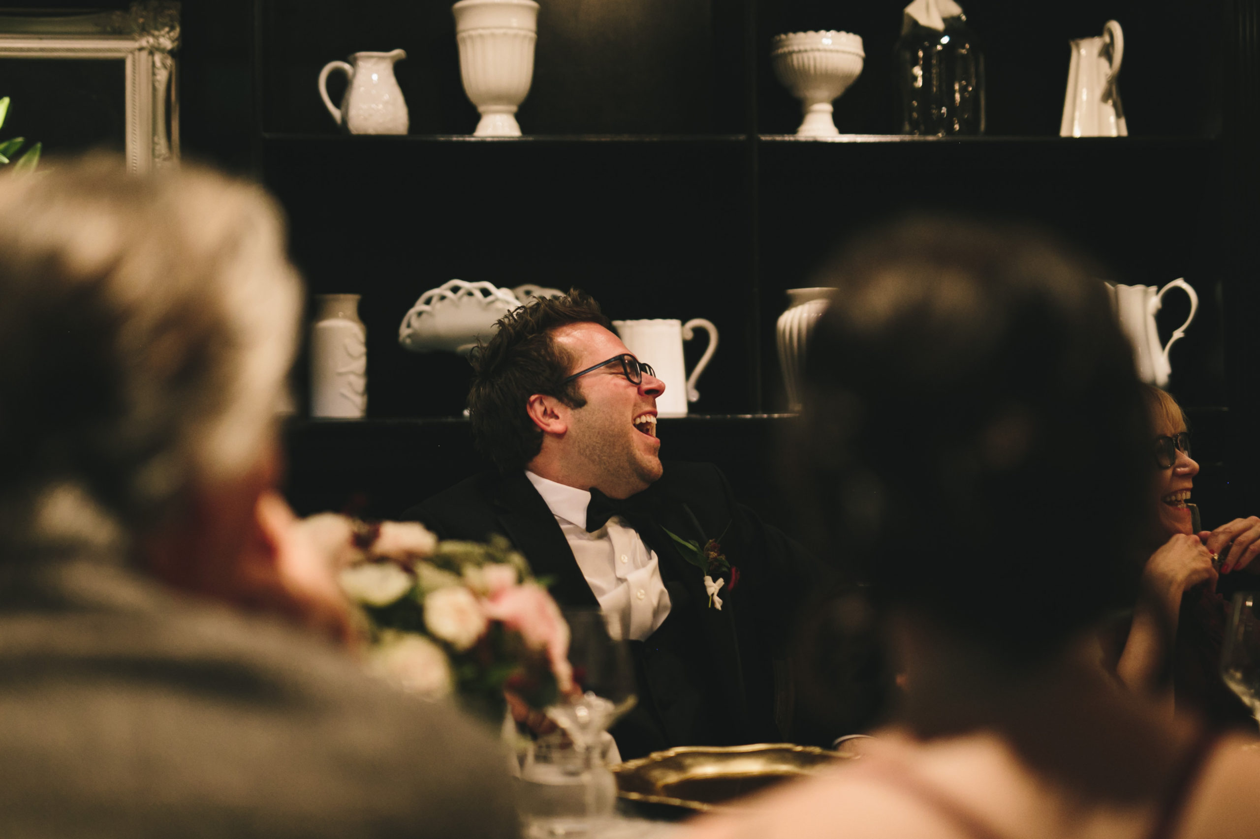 Groom laughing during wedding toasts